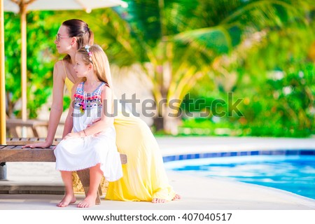 Young mother and daughter relaxing near swimming pool