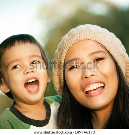 Young mother and her cute son smiling together on an autumn day.