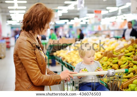 Young mother and her cute toddler boy in a food store or a supermarket