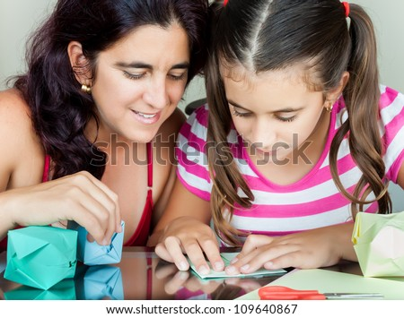 Young mother and her daughter making paper models or origami