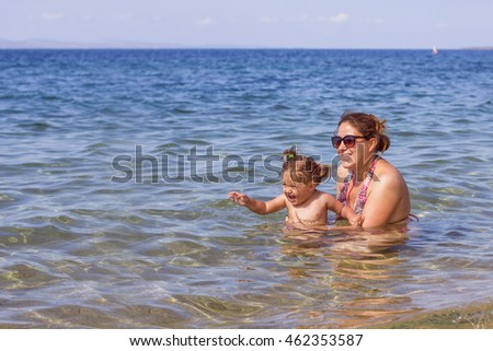 Young Mother and her little girl have fun in the beautiful turquoise sea on summer day. Travel Vacation lifestyle.