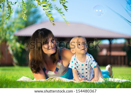 Young mother and her little son looking at soap bubbles