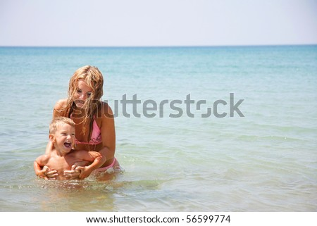 young mother and son playing in water