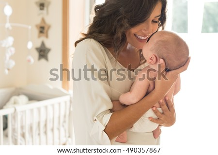 Young mother holding her baby in the bedroom