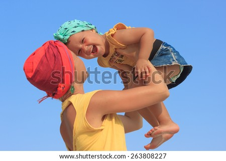 Young mother hugging her daughter on the beach dressed similar clothes view 3