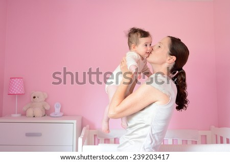 Young mother kisses her baby (girl age 06 months). Concept photo parenthood and motherhood.