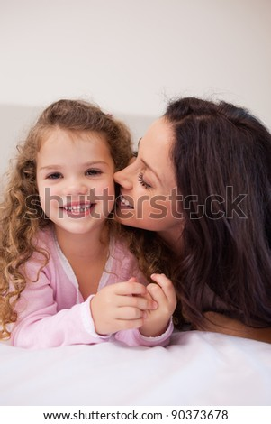 Young mother kissing her daughters cheek