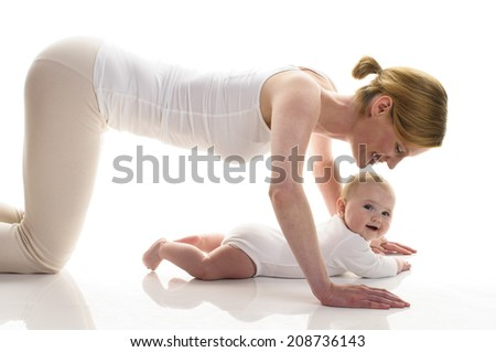 Young mother makes with her 6 month old daughter postnatal exercises, isolated against white background. She kneels on the ground and makes about the baby pushups.