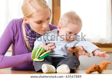 young mother plays with her baby with toys