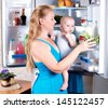 Young mother with a child takes food out of the fridge. Storing food in the refrigerator. A child in the arms of mother. - stock