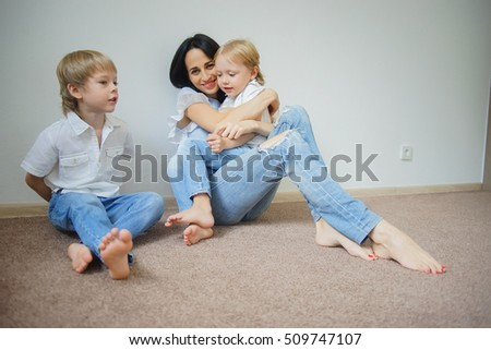 Young mother with her little sons are relaxing and playing at the weekend together, warm and cozy scene. Selective focus.