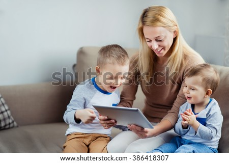 Young mother with her 2 years old little son and 5 years old son playing with digital tablet at home