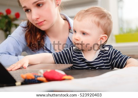 Young mother working with her baby at home