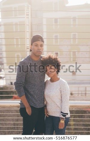 Young multiethnic couple outdoor in the city hugging - friendship, relationship, togetherness concept