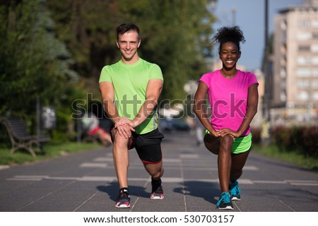Young multiethnic jogging couple warming up and stretching before morning running in the city