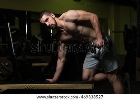 Young Muscular Man Doing Heavy Weight Exercise For Triceps With Dumbbell In Gym