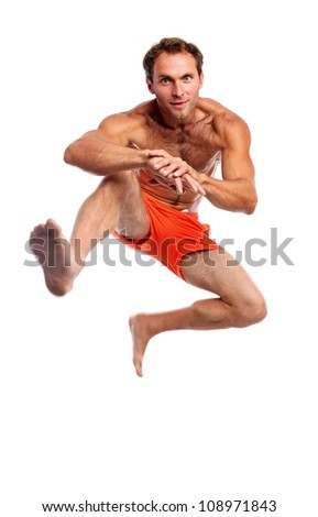 Young muscular man jumping against white background