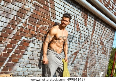 Young muscular man leaning against brick wall outdoors.