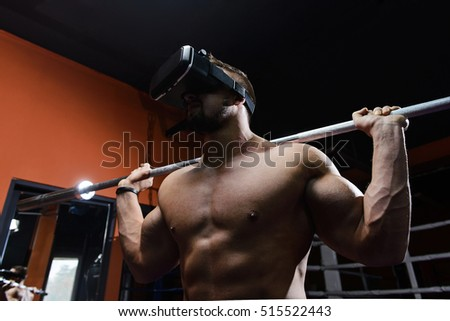 Young muscular man with vr headset and with barbell on shoulders during indoor workout in gym.Selective focus/Fit man during virtual workout
