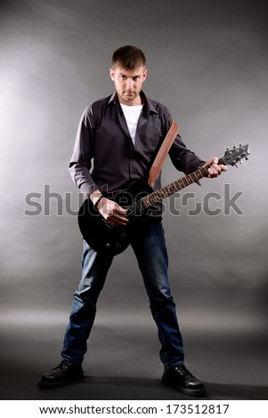 Young musician playing  guitar on gray background
