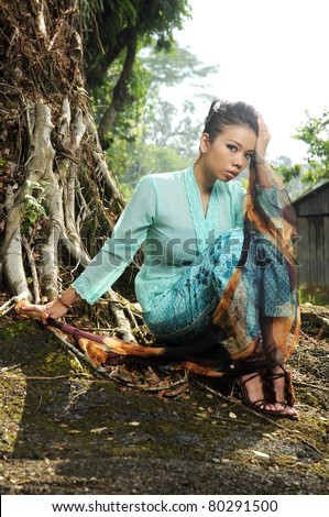 Young muslim woman sit on the old tree root with hand on her head isolated old town