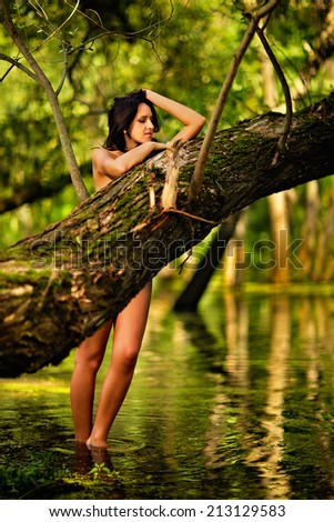 Young naked beautiful Caucasian woman standing in water in rainforest with eyes closed, hiding behind a tree.