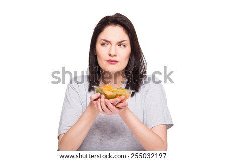 young natural woman looking bored with her healthy meal, isolated on white
