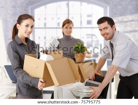 Young office workers moving office, unpacking boxes, smiling.?