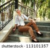 Young old fashioned girl sitting on the stage of vintage building - stock photo