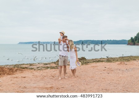 young parents playing with their little son on the sea. son on the shoulders of dad