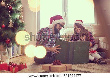 Young parents sitting on the living room floor next to a nicely decorated Christmas tree, mother holding a baby girl in her lap and all together reading a fairy tale