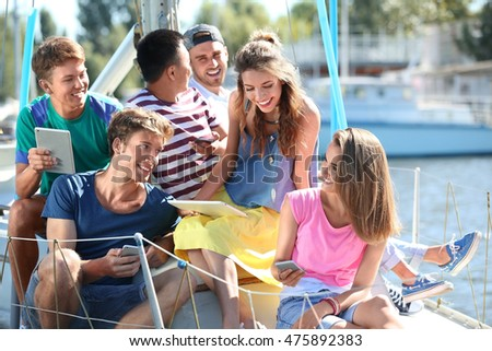 Young people with gadgets hanging out on a yacht