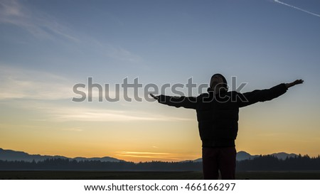 Young person celebrating the sunrise or sunset standing with outstretched arms silhouetted against a colorful orange sky.