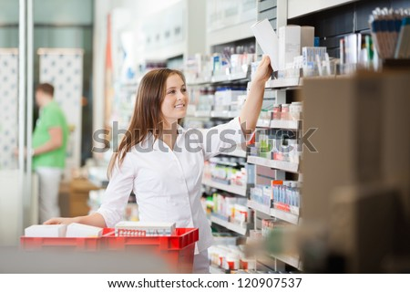Young pharmacist stocking shelves in pharmacy