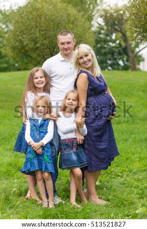 Young pregnant mother with her family in a park. Family resting in a nature. Pregnancy