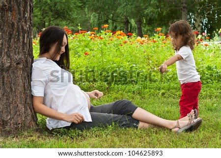 Young pregnant woman and her little baby girl in a summer garden