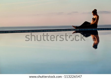 Young pregnant woman at sunrise sitting on edge of pool