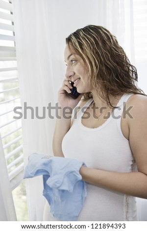 Young pregnant woman holding baby clothing while answering phone call