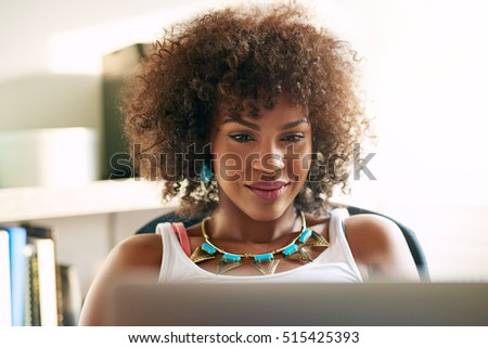 Young pretty afro-american woman looking at desk-top and smiling on blurred inside background.