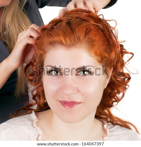 young pretty blond girl making hairstyle to her friend