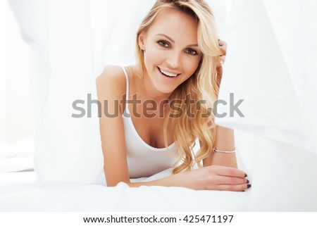 young pretty blond woman in bed covered white sheets smiling cheerful sexy look close up