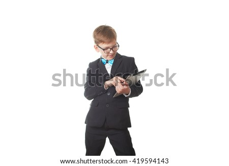 Young pretty boy posing at studio as a fashion model. Photo of preschooler 9 years old isolated on over white background with tablet