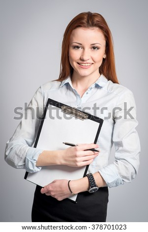 Young pretty business woman with tablet paper isolated on grey background