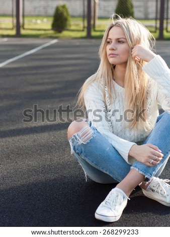 Young pretty fashionable blonde woman dressed in ripped jeans and white sweater sitting on the ground in summer and having fun
