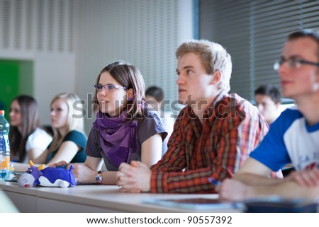 young, pretty female college student sitting in a classroom full of students during class