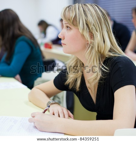 young pretty female college student sitting in a classroom full of students during class (shallow DOF; color toned image)