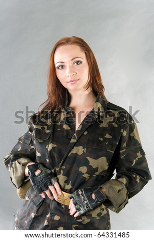 Young pretty female model in military outfit with water flask and USSR star belt in studio