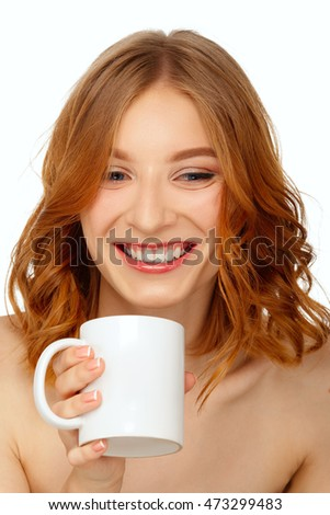 Young pretty girl drinks from big white cup. Natural make-up.