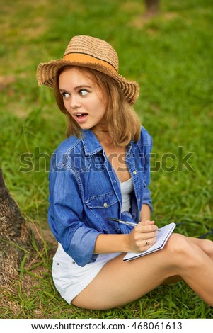 Young pretty girl loudly and emotionally answer to the question. Sitting in the park in a casual clothes and stylish hat, writing in the notebook.