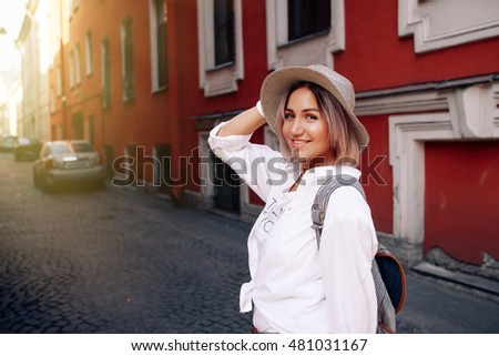 Young pretty hipster cheerful girl posing on the street at sunny day, having fun alone, stylish vintage clothes hat. travel concept